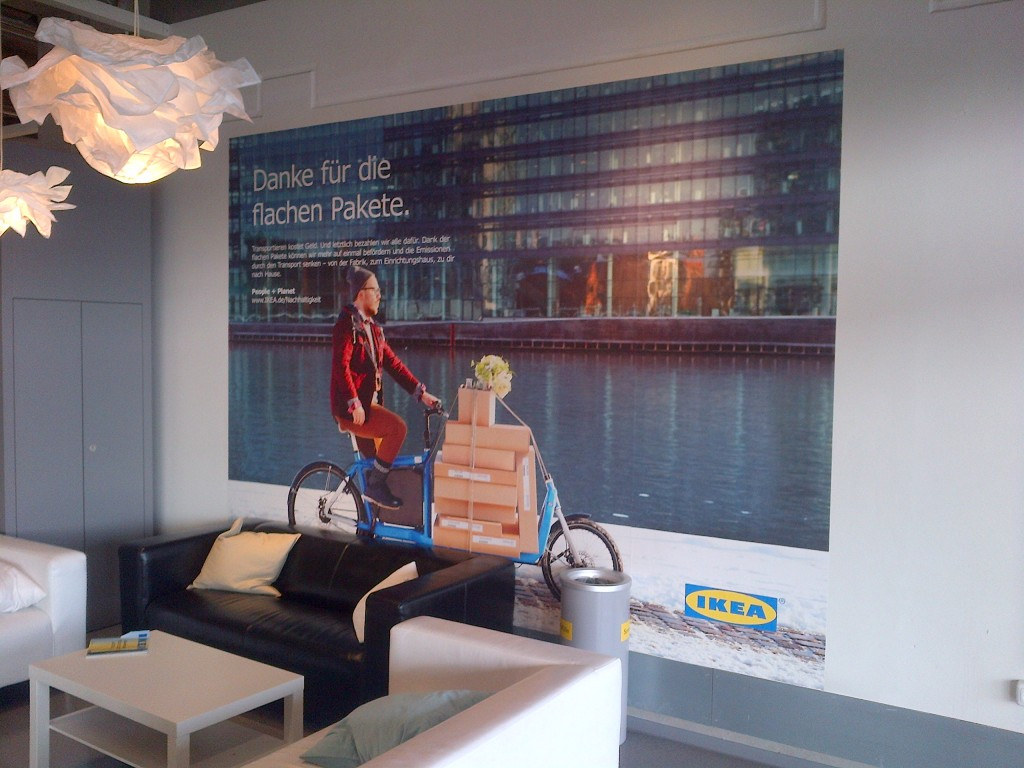 Plakat im Wartebereich der IKEA-Warenausgabe zeigt ein mit Kartons beladenes Bullitt.